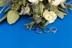 Dois alianças de casamento e aneis de noivado dourados com um diamante no fundo azul foto de stock royalty free