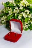 Dois alianças de casamento e lírios do vale fotografia de stock royalty free