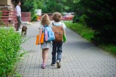 Dois alunos da escola primária vão guardar as mãos fotografia de stock