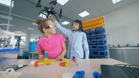 Dois alunos que fixam o zangão modelam na turma escolar moderna da tecnologia 4K video estoque