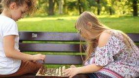 Dois alunos que jogam a xadrez no parque no banco F?rias de ver?o, jogos intelectuais video estoque