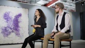 Dois amantes da arte estão apreciando a arte finala moderna na galeria e no guia audio de escuta video estoque