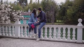 Dois amantes devem sentar-se em um jardim de florescência bonito e beijar-se video estoque