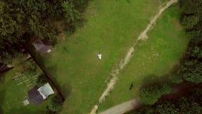 Dois amantes dos povos encontram-se na grama verde ao lado deles A câmera voa lentamente longe deles Tiro de Quadcopter filme