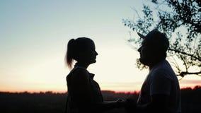 Dois amantes menino e posição da menina no banco alto do rio contra o por do sol bonito e para olhar se video estoque