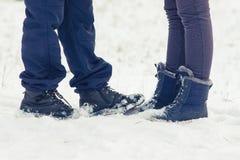Dois amantes novos estão em um dia de inverno na neve, girando para e Foto de Stock