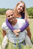 Dois amantes novos que prendem-se andam às cavalitas Imagens de Stock