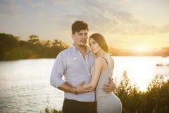 Dois amantes que embrassing no por do sol foto de stock