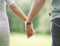 Dois amantes que guardam-se delicadamente mãos do ` s e que andam no Imagens de Stock