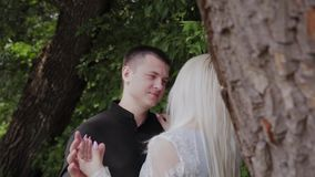 Dois amantes sentam-se sob uma árvore no tempo ensolarado olham se e o sorriso vídeos de arquivo