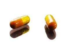 Dois amarelos e comprimidos alaranjados da cor Foto de Stock