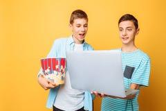 Dois amigos adolescentes com uma cubeta da pipoca em suas mãos e em um portátil que prepara-se para olhar filmes em um fundo amar fotografia de stock royalty free