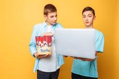 Dois amigos adolescentes com uma cubeta da pipoca em suas mãos e em um portátil que prepara-se para olhar filmes em um fundo amar fotos de stock royalty free
