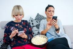 Dois amigos atrativos da mulher com telefone celular e pipoca imagens de stock