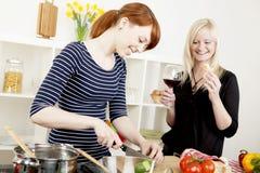 Amigos das mulheres que preparam uma refeição Fotografia de Stock
