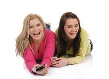 Dois amigos bonitos da mulher que prestam atenção à televisão Foto de Stock