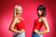 Dois amigos bonitos no estúdio em um fundo cor-de-rosa que levanta no short imagem de stock