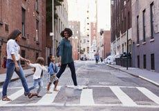 Dois amigos da mãe com as duas filhas que cruzam a estrada foto de stock
