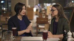 Dois amigos das jovens mulheres que falam no café da noite fora vídeos de arquivo