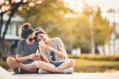 Dois amigos das mulheres sentam-se no parque e relaxam-se em um feriado feliz fotografia de stock royalty free