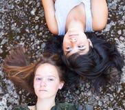 Dois amigos de adolescente que encontram-se em um fundo do granito Imagens de Stock Royalty Free