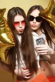 Dois amigos de adolescentes com balões do ouro fazem o selfie em um p Fotos de Stock