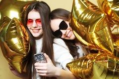 Dois amigos de adolescentes com balões do ouro fazem o selfie em um p Fotografia de Stock