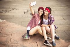Dois amigos de adolescentes morenos no moderno equipam o shor das calças de brim Foto de Stock Royalty Free