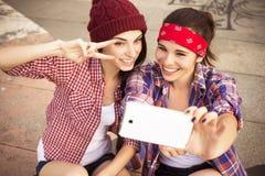 Dois amigos de adolescentes morenos no moderno equipam o shor das calças de brim Imagem de Stock