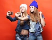 Dois amigos de adolescentes no equipamento do moderno fazem o selfie em um pho Imagem de Stock