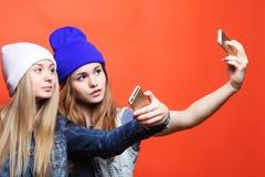 Dois amigos de adolescentes no equipamento do moderno fazem o selfie em um pho Foto de Stock Royalty Free
