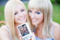 Dois amigos de menina com uma câmera da foto foto de stock royalty free
