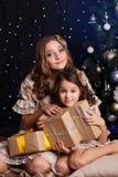 Dois amigos de meninas com presentes aproximam a árvore de Natal imagem de stock royalty free
