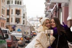 Dois amigos de meninas positivos que tomam a um autorretrato na cidade nos Imagem de Stock Royalty Free