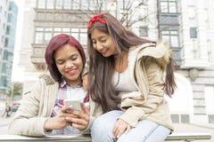 Dois amigos de sorriso da mulher que compartilham de meios sociais em um telefone esperto Imagens de Stock Royalty Free
