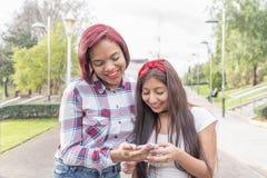 Dois amigos de sorriso da mulher que compartilham de meios sociais em um telefone esperto Imagem de Stock