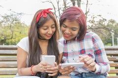 Dois amigos de sorriso da mulher que usam o telefone esperto Fotografia de Stock Royalty Free