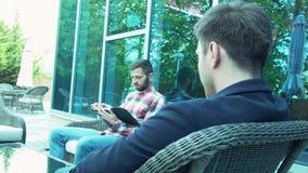 Dois amigos de um homem de negócios comunicam-se em um restaurante no ar fresco Um homem novo com uma tabuleta senta-se em um vim vídeos de arquivo