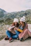 Dois amigos envolvidos em uma cobertura estão sentando-se no prado quando removerem uma garrafa térmica para preparar um caldo foto de stock royalty free