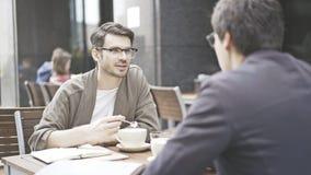 Dois amigos estão bebendo o coffe que falam fora Fotos de Stock