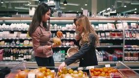 Dois amigos estão escolhendo as frutas e legumes no supermercado vídeos de arquivo
