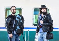 Dois amigos estão esperando o trem para vir Imagem de Stock