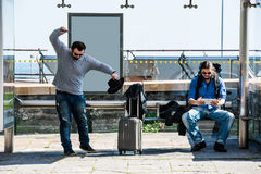 Dois amigos estão ficando com raiva devido ao atraso do ônibus Foto de Stock