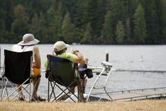 Dois amigos estão relaxando na costa do lago da montanha na floresta foto de stock