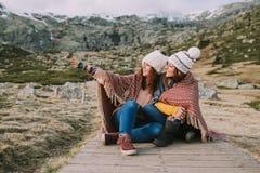 Dois amigos estão sentando-se no prado envolveram em uma cobertura enquanto olham e apontam a um lugar imagens de stock royalty free