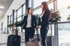 Dois amigos fêmeas alegres que esperam um plano que está no salão do aeroporto com bagagem pesada perto das portas imagem de stock royalty free