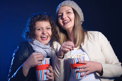 Dois amigos fêmeas bonitos que riem felizmente e filme de observação fotos de stock royalty free