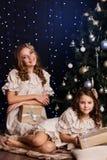 Dois amigos fêmeas com presentes aproximam a árvore de Natal foto de stock