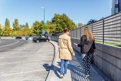 Dois amigos fêmeas conversam ao andar quietamente para baixo uma rua, em um dia bonito foto de stock