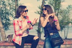 Dois amigos fêmeas felizes que bebem o café e que têm o divertimento Natureza do fundo, parque, rio Conceito urbano do estilo de  imagens de stock royalty free